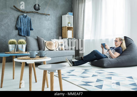 Modern style interior in grey with sofa, stylish futniture, man sitting on a bean bag - Stock Photo
