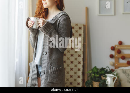 Smiling woman in sweater looking through the window - Stock Photo