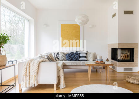 White sofa with pillows and modern fireplace in stylish living room - Stock Photo