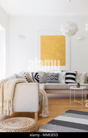 Wool blanket and pillows on white sofa in stylish living room - Stock Photo