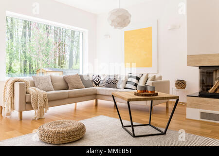Wooden coffee table and white sofa in cozy trendy designed living room - Stock Photo