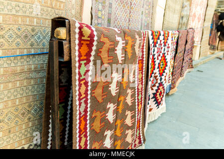 Group of precious ancient colored wool Azeri ancient carpets made by hand in ancient city at Carpet store. - Stock Photo
