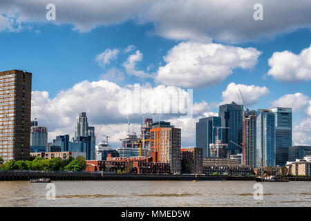 London, Isle of Dogs City skyline view. New-build luxury apartment buildings under construction and Canary Wharf Financial district - Stock Photo