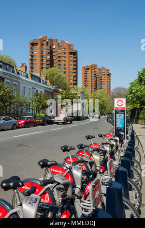 A Santander docking station on Lots Road, Chelsea, overlooking the World's End council estate on King's Road, London, UK - Stock Photo