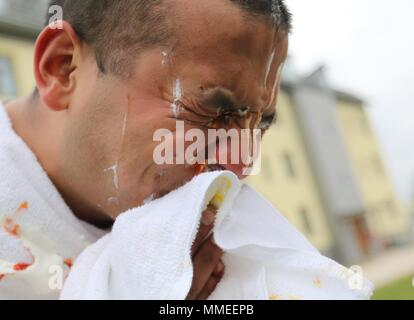 Sgt. Issac Gonzalez, operations noncommissioned officer assigned to 7th Army Training Command's Headquarters and Headquarters Company, removes the remains of a whip cream, mustard and ketchup pie from his face in Graffenwoehr, Germany, May 11, 2018, May 11, 2018. Soldiers from 7ATC conducted a pie-in-the-face event to raise money for the Army Emergency Relief campaign. So far the event has raisied over 400 dollars in an hour. (U.S. Army photo by Sgt. Marlon Styles). () - Stock Photo