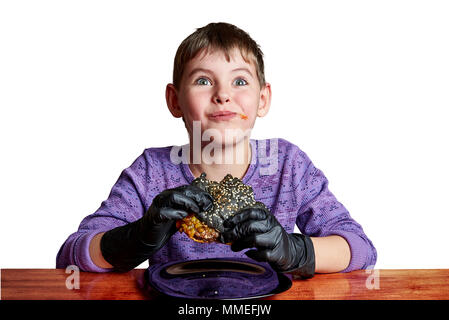 Boy in black gloves emotionally eating a burger at the table on a white background - Stock Photo