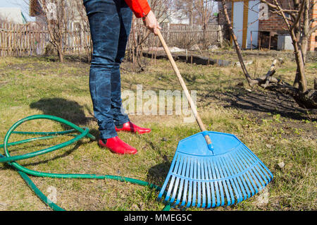 Young woman farmer working in the garden, rake clears the lawn, garden tools - Stock Photo