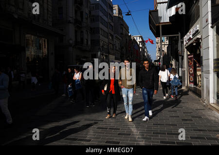 Istanbul, Turkey - April 19, 2018: Arap ethnicity tourists are walking at The Istiklal Street, Beyoglu in a sunny springtime day. There are many store - Stock Photo