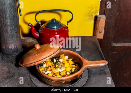 Old firewood kitchen where they are cooking a meal, the fire is visible and a red teapot - Stock Photo