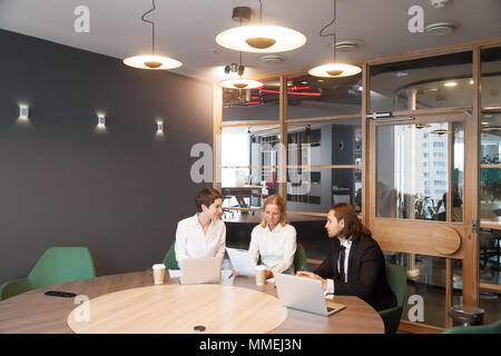 Businesspeople having discussion at team meeting in modern offic - Stock Photo