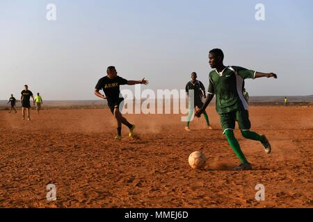 U.S. Army infantry soldiers from 10th Mountain Division and 3-144 Infantry Regiment and members of the Djibouti Armed Forces (FAD) assigned to the Rapid Intervention Battalion, play soccer in Djibouti May 10, 2018, May 10, 2018. Members of the RIB go through a five week course covering combatives, weapons, and combat lifesaving skills. (U.S. Air Force photo by Airman 1st Class Haley D. Phillips). () - Stock Photo