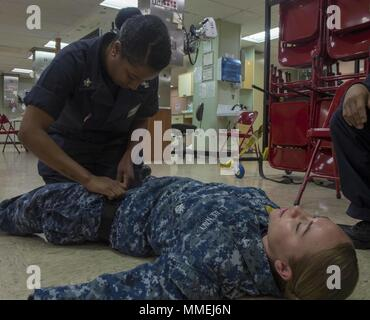 180511-N-NH199-0134 PACIFIC OCEAN (May 11, 2018) Hospital Corpsman 1st Class Stacie Coursey (left), from Fairfield, Calif. applies a tourniquet during a tactical combat causality care (TCCC) course aboard Military Sealift Command hospital ship USNS Mercy (T-AH 19), May 10, 2018. Mercy is currently deployed in support of Pacific Partnership 2018 (PP18). PP18's mission is to work collectively with host and partner nations to enhance regional interoperability and disaster response capabilities, increase stability and security in the region, and foster new and enduring friendships across the Indo- - Stock Photo