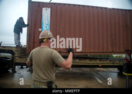 U.S. Navy Equipment Operator 3rd Class Xavier Fay, assigned to Naval Mobile Construction Battalion (NMCB) 4, signals to the crane operator as a container is lowered for transport on Kadena Air Force Base in Okinawa, Oct. 27, 2017. NMCB 4 recently deployed to Okinawa as the forward deployed NMCB, ready to support Major Combat Operations, Humanitarian Assistance and Disaster Relief operations. They provide general engineering and civil support to Navy, Marine Corps and joint operational forces. Homeported out of Port Hueneme, Calif., NMCB 4 has 11 detached sites deployed throughout the United St - Stock Photo