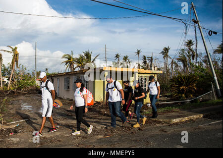 Volunteers from A la mano por Puerto Rico, walk through a residential neighborhood in Humacao, Puerto Rico, Oct. 28, 2017. A la mano por Puerto Rico, which stands for 'On hand for Puerto Rico,' is a local non-profit organization comprised of Puerto Rican athletes and volunteers committed to providing medical attention, water and food in times of crisis.  (U.S. Air Force photo by Tech. Sgt. Larry E. Reid Jr.) - Stock Photo