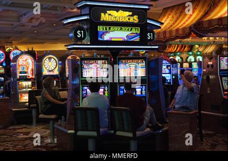 Gamblers playing Megabucks slot machines, Bellagio Casino, Las Vegas, Nevada. - Stock Photo