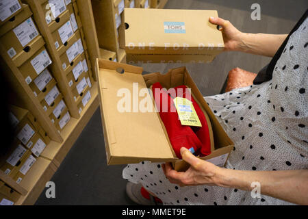 A discerning shopper chooses Toms brand footwear in a shoe store in New York on Thursday, May 3, 2018. Because of debt incurred in 2004 when it was taken over by Bain Capital the cobbler Toms is struggling with the so-called retail apocalypse. (© Richard B. Levine) - Stock Photo