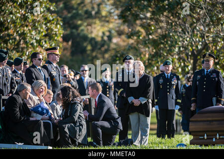 Karen Durham-Aguilera, executive director, Army National Military Cemeteries; and Ryan McCarthy, acting secretary, U.S. Army; kneel in front of U.S. Army Staff Sgt. Bryan Black's family to pay condolences for their loss while Gen. Mark Milley, chief of staff, U.S. Army, and his wife, Hollyanne, wait to the side at the graveside service for Black in Section 60 of Arlington National Cemetery, Arlington, Virginia, Oct 20, 2017. Black, a native of Puyallup, Washington, was assigned to Company A, 2nd Battalion,3rd Special Forces Group (Airborne) on Fort Bragg, North Carolina when he died from woun - Stock Photo
