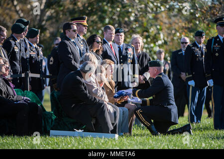 Michelle Black received the American flag during the graveside service for her husband, U.S. Army Staff Sgt. Bryan Black, in Section 60 of Arlington National Cemetery, Arlington, Virginia, Oct. 30, 2017.  Black, a native of Puyallup, Washington, was assigned to Company A, 2nd Battalion,3rd Special Forces Group (Airborne) on Fort Bragg, North Carolina when he died from wounds sustained during enemy contact in the country of Niger in West Africa, Oct. 4, 2017.  Ryan McCarthy, acting secretary, U.S. Army; Gen. Mark Milley, chief of staff, U.S. Army; and Karen Durham-Aguilera, executive director, - Stock Photo