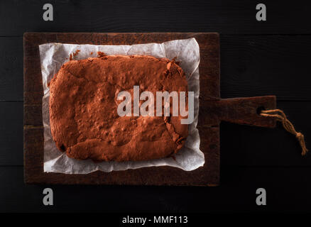 square whole baked brownie pie on a brown wooden board, top view - Stock Photo