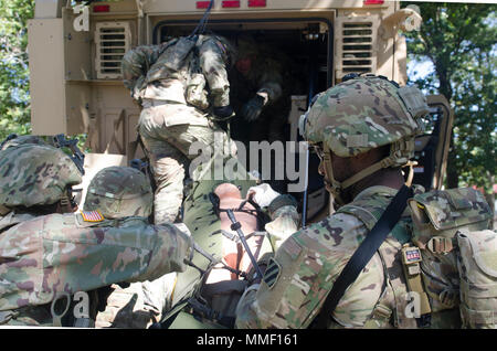 Soldiers assigned to 5th Battalion, 1st Security Force Assistance Brigade prepare to maneuver towards a medical evacuation point Oct. 24, 2017, at Ft. Benning, Ga. The MEDEVAC lane challenged combat advisory teams to assess simulated injuries and call for an evacuation at a designated location. Soldiers interested in joining the 1st SFAB should contact their branch manager for more information. (U.S. Army photo by Sgt. Arjenis Nunez/Released) - Stock Photo