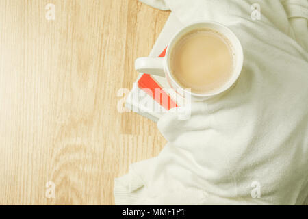 Cup of coffee, white cloth and stack of books on top of wood background. Morning breakfast. Top view. - Stock Photo