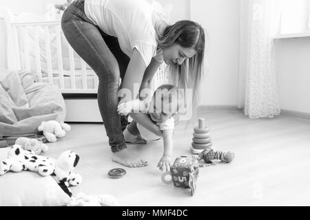 Black and white image of young mother trying to calm down her crying baby boy - Stock Photo