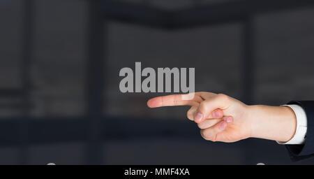 Hand pointing on dark background - Stock Photo