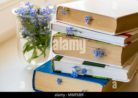 A stack of books with small blue flowers between pages on white table - Stock Photo