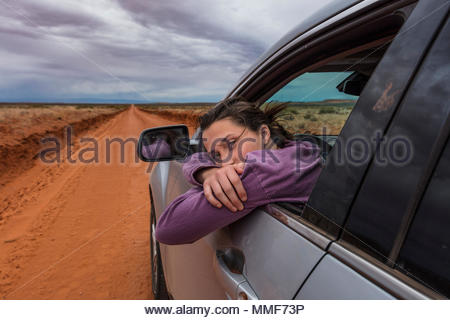 A teen girl pauses on a drive down the long straight dirt road that leads to Canyonlands National Park. - Stock Photo