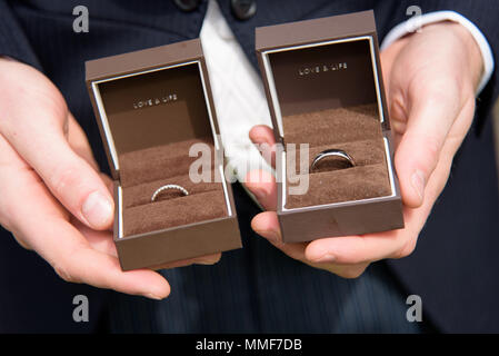 Best Man holding Wedding rings in boxes with words Love & Life inside - Stock Photo