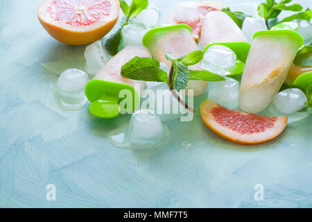 Homemade grapefruit popsicles with grapefruit slices on a mint wooden background. Top view. Copy space. Flat lay - Stock Photo