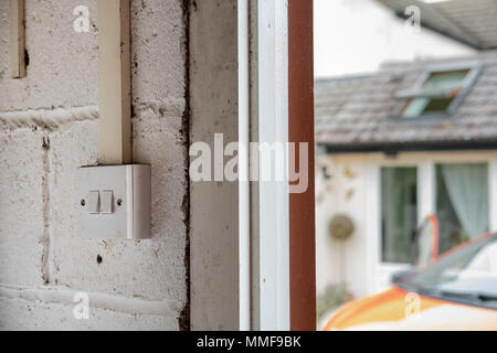 Isolated view of double range garage switches seen adjacent to opened garage doors. The background shows an out of focus car and back of house. - Stock Photo