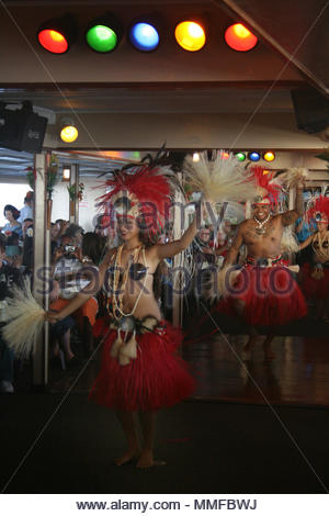 Hawaiian dancers performs for tourists aboard cruise ship in Honolulu. - Stock Photo