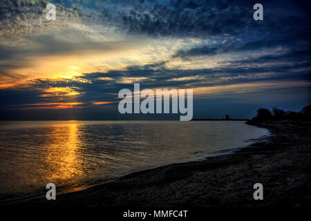 Beautiful vibrant sunrise over Lake Erie from Magee Marsh Ohio. Davis-Besse nuclear power plant can be seen in the distance. - Stock Photo