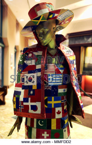 A mannequin decorated in various flags from around the globe. - Stock Photo