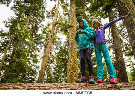 Two young girls enjoy walking along a fallen log in the forest. - Stock Photo