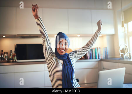 Excited young Muslim female entrepreneur wearing a hijab raising her arms in success while working in her kitchen on a laptop - Stock Photo