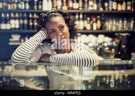 Young African cafe owner smiling and looking deep in thought while leaning on the counter of her trendy cafe