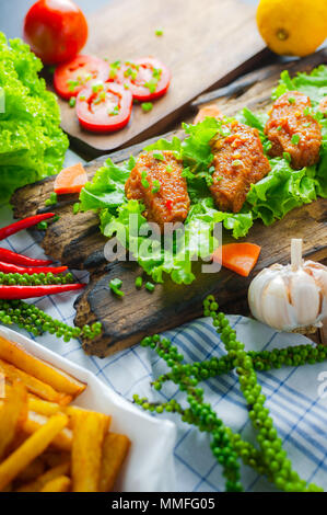 Fried chicken wings with spicy chilli sauce on rustic serving board, herbs and vegetable over wooden background. - Stock Photo