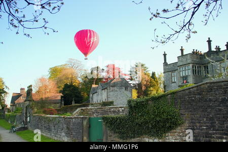 Tissington Hall, Peak District, Derbyshire, UK. A hot air balloon soars above Tissington Hall in the Peak District National Park, England, UK - Stock Photo