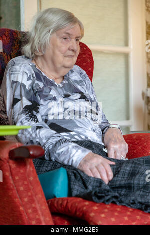 11 May 2018 - Old lady suffering from Dementia sits alone with her bare feet raised up in her red recliner chair watching the television - Stock Photo