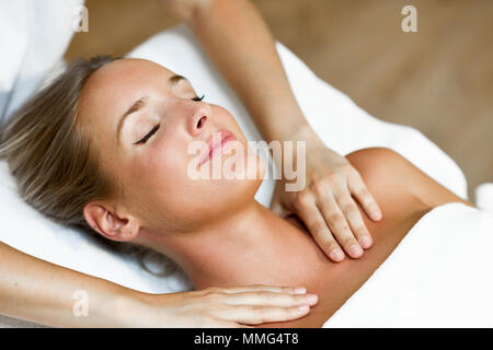 Young blond woman receiving a head massage in a spa center with eyes closed and smiling. Female patient is receiving treatment by professional therapi - Stock Photo