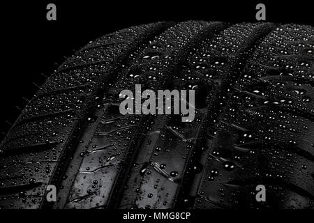 Close up view of a car tyre isolated on a black background with water drops - Stock Photo