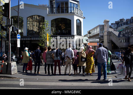 A busy Boulevard Barbès, Paris, France, with Brasserie Barbes in background - people waiting to cross the road - Stock Photo