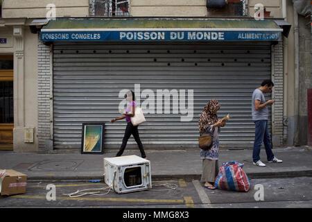 Woman in headscarf finds book among rubbish, Poisson du Monde, Rue de Suez, Goutte d'Or, Paris, France - Stock Photo