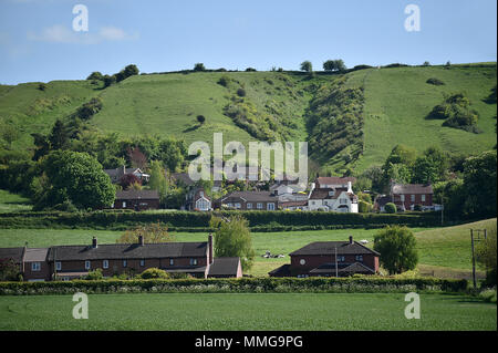 Village homes seen at the bottom of the hill in the Wiltshire village of Edington in Springtime - Stock Photo