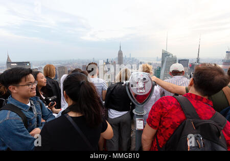 Tourists around a telescope on the Top of the Rock observation platform, Rockefeller center, New York city, USA - Stock Photo