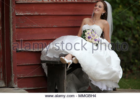 A bride in a traditional white wedding dress holding a bouquet of roses. - Stock Photo