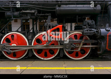 fragment of vintage functioning steam locomotive standing at station, closeup, visible driving wheels with a system of pistons, connecting rods and le - Stock Photo