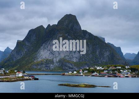 Mount Olstind and Reine fishing village on Lofoten islands - Stock Photo